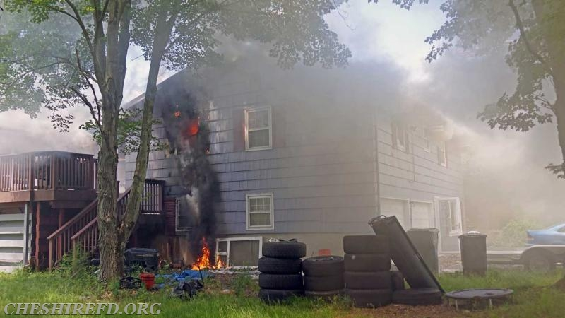 Fire venting from a bedroom with burning debris dropping down and igniting materials on the ground and exterior of the structure.