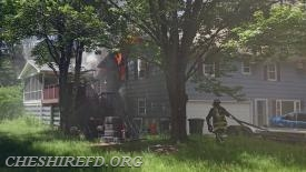 A Cheshire Firefighter works to stretch a hose line to the rear of the residence.