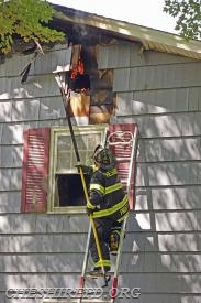 FF Pruitt works to remove burning sections of siding and sheathing from the exterior.